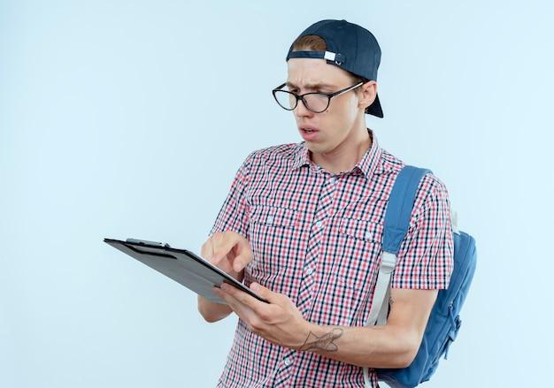 Garoto jovem estudante confuso usando mochila, óculos e boné segurando e olhando para a prancheta