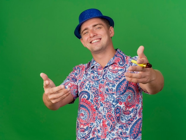 Garoto jovem sorridente com chapéu azul, segurando o soprador de festa e estendendo as mãos para a câmera, isolado sobre fundo verde