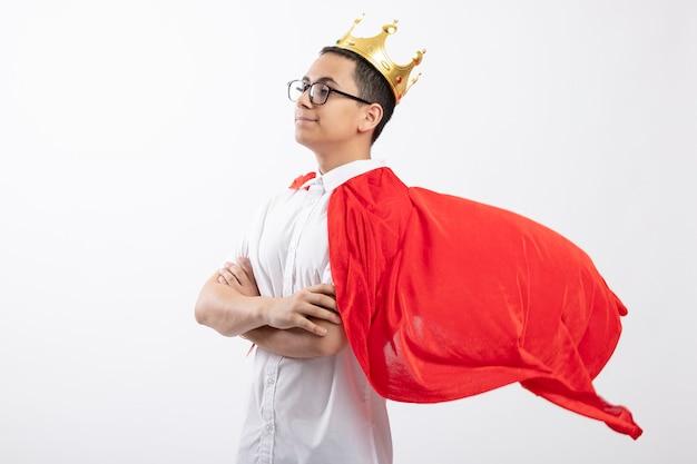 Garoto jovem super-herói confiante com capa vermelha usando óculos e coroa em pé com postura fechada em vista de perfil, olhando diretamente isolado no fundo branco com espaço de cópia