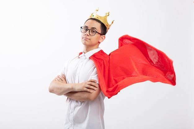 Garoto jovem super-herói confiante com capa vermelha usando óculos e coroa em pé com postura fechada em vista de perfil, olhando para a câmera isolada no fundo branco com espaço de cópia