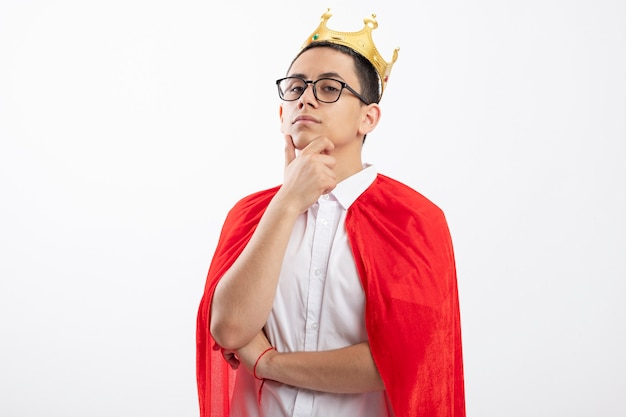 Garoto jovem super-herói confiante com capa vermelha usando óculos e coroa, olhando para a câmera, tocando o queixo isolado no fundo branco com espaço de cópia