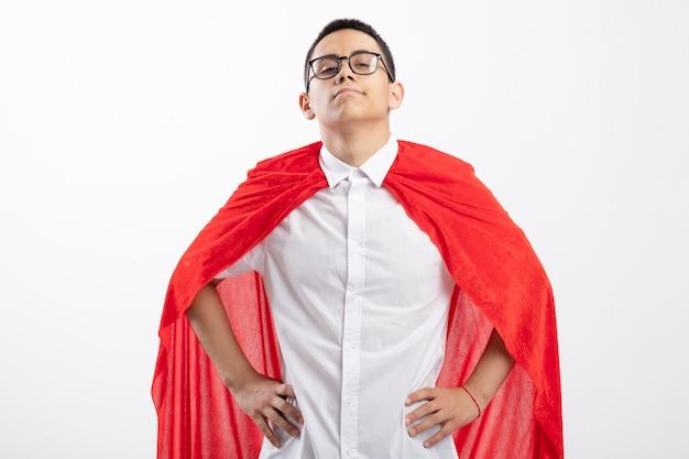 Garoto jovem super-herói confiante com capa vermelha usando óculos, olhando para a câmera e mantendo as mãos na cintura, isoladas no fundo branco