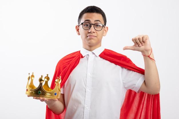 Garoto jovem super-herói confiante com capa vermelha usando óculos segurando uma coroa, olhando para a câmera apontando para si mesmo, isolado no fundo branco