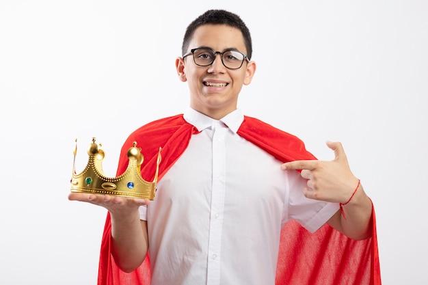 Garoto jovem super-herói sorridente com capa vermelha usando óculos, segurando e apontando para a coroa, olhando para a câmera isolada no fundo branco