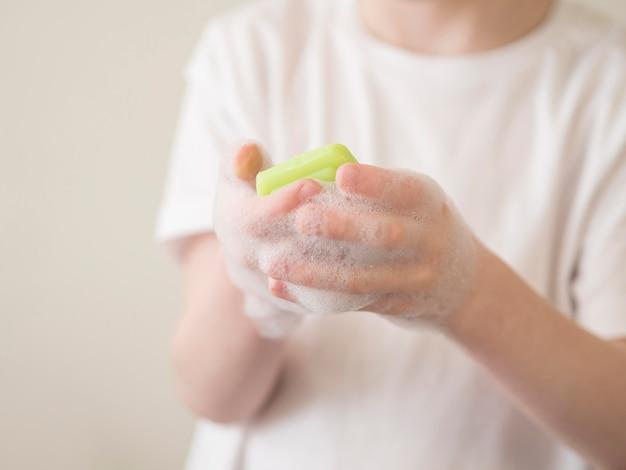 Garoto lavando as mãos com sabão