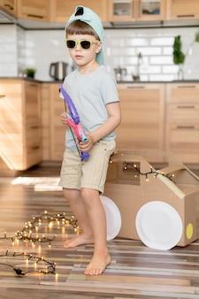 Garoto legal de tiro completo segurando o brinquedo de arco