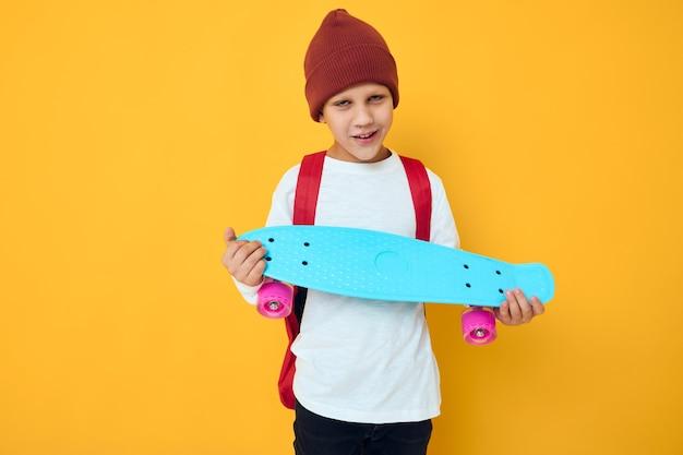 Garoto legal e sorridente em um estilo de vida de estúdio de entretenimento de skate de suéter branco