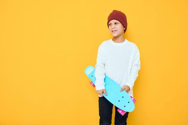 Garoto legal e sorridente em um skate de chapéu vermelho com as mãos em um fundo de cor amarela