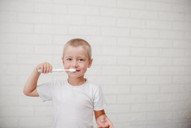 Garoto limpando os dentes. criança pequena com uma parede de pincel branco