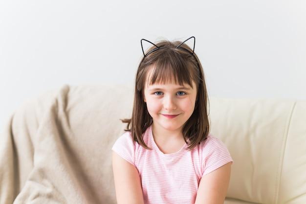 Garoto linda garota com orelhas de gato sentado no sofá. crianças e conceito de infância.