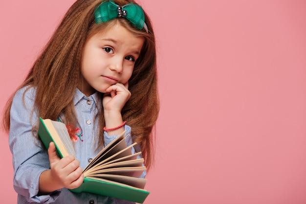 Garoto linda garota pensativa, com longos cabelos castanhos, sustentando a cabeça com a mão enquanto lê o livro ou informações de aprendizagem
