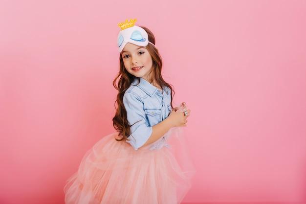 Garoto lindo lindo carnaval se divertindo isolado no fundo rosa. menina bonita com longos cabelos castanhos, saia de tule, máscara de princesa expressando felicidade para a câmera, comemorando festa infantil