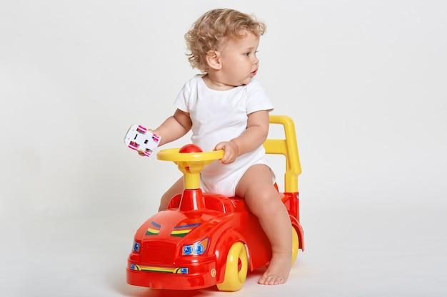 Garoto lindo no espaço claro brincando com a máquina tolocar, segurando o carrinho nas mãos, olhando para o lado com interesse