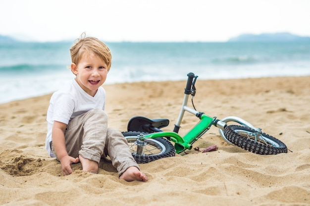 Garoto loiro ativo dirigindo bicicleta no parque perto do mar