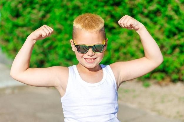 Garoto loiro bonito com óculos de sol mostra os músculos da natureza no verão