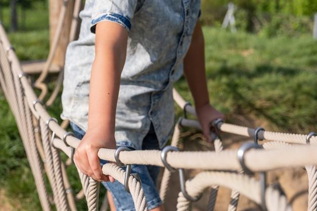 Garoto loiro bonito subindo no parquinho de madeira em um parque de cordas. garoto brinca ao ar livre em um dia ensolarado de verão