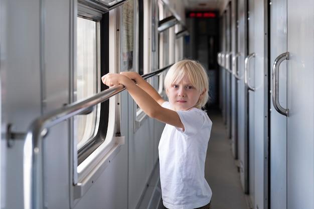 Garoto loiro bonito viajando de trem