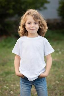 Garoto loiro com cabelos longos ao ar livre