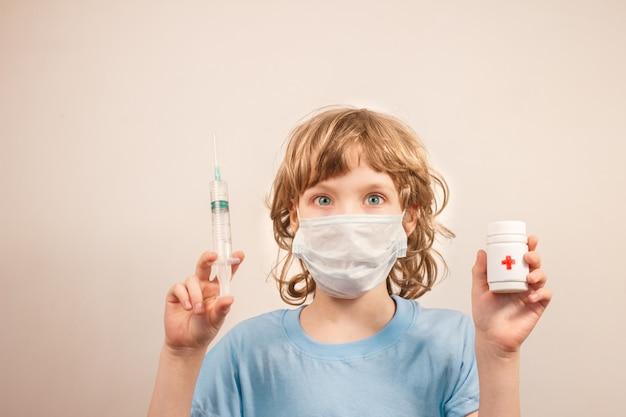 Garoto loiro com máscara cirúrgica e segurando a seringa com vacina e frasco branco com comprimidos nas mãos, propagação de infecção e conceito de contaminação