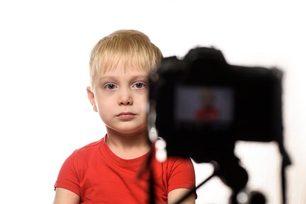 Garoto loiro sério está gravando um vídeo na câmera dslr. pequeno blogueiro de vídeo. fundo branco