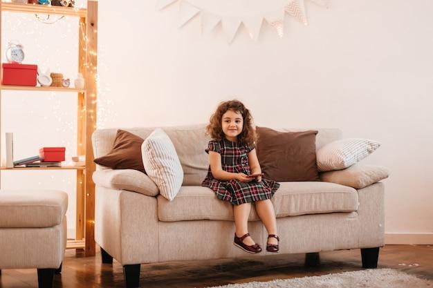Garoto maravilhoso sentado na sala de estar. foto interna da menina pré-adolescente com vestido posando no sofá.