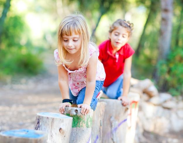 Garoto meninas brincando em troncos na natureza da floresta
