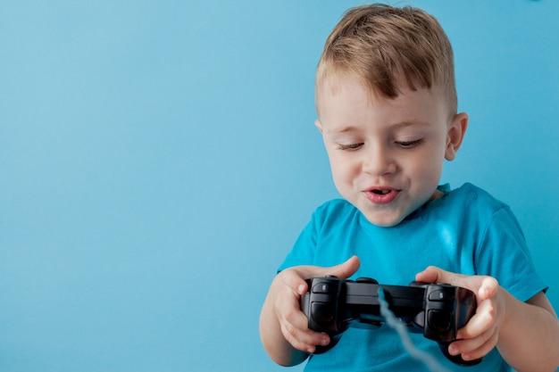 Garoto menino, 2-3 anos de idade, vestindo roupas azuis segurar joystick na mão para gameson fundo azul