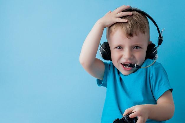 Garoto menino 2-3 anos vestindo roupas azuis segura o joystick na mão para o retrato de estúdio de crianças gameson azul. conceito de estilo de vida de infância de pessoas. simule o espaço da cópia.
