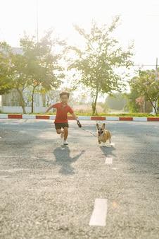 Garoto menino corre na rua com seu cachorro de estimação
