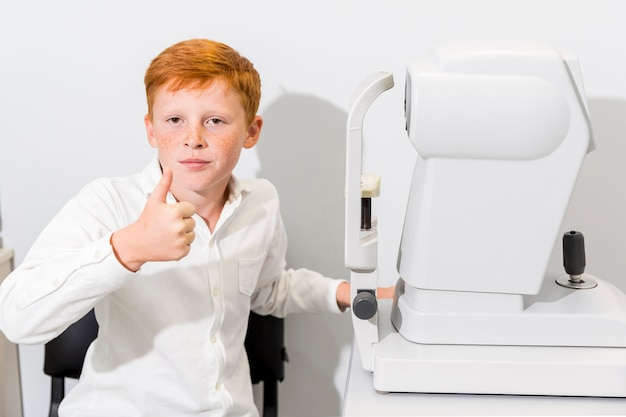 Garoto mostrando o polegar para cima gesto sentado perto da máquina de refratômetro na clínica de óptica