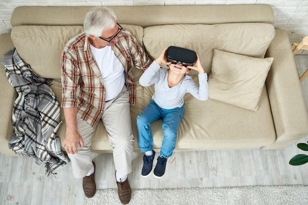 Garoto mostrando tecnologias modernas ao vovô