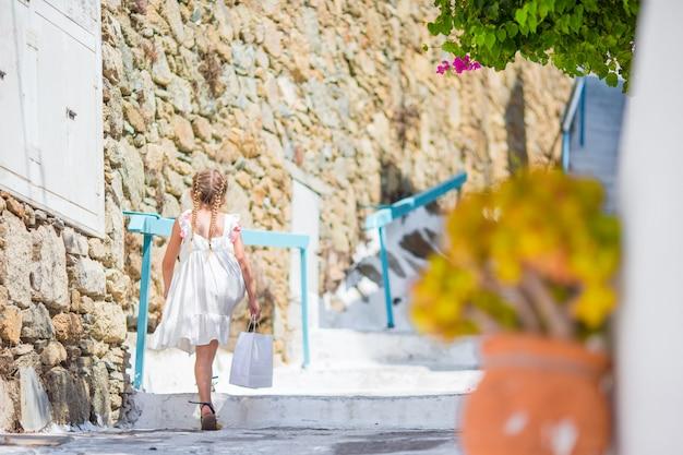Garoto na rua da aldeia tradicional grega típica com escadas brancas na ilha grega