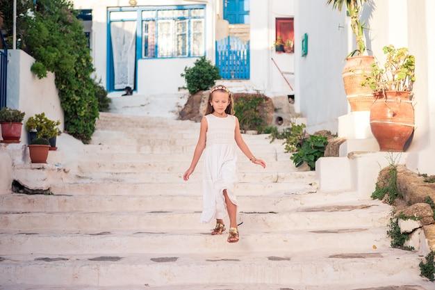 Garoto na rua da aldeia tradicional grega típica com paredes brancas e portas coloridas na ilha de mykonos