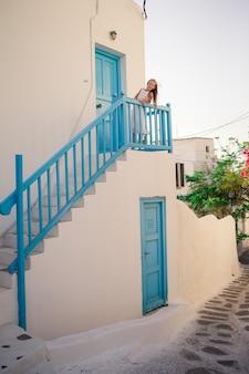 Garoto na rua da aldeia tradicional grega típica com paredes brancas e portas coloridas