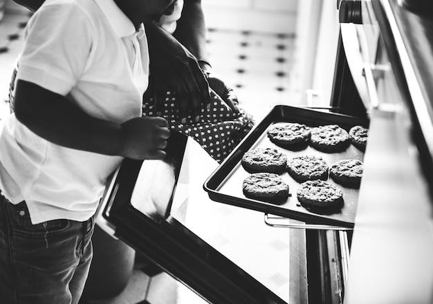 Garoto negro, ajudando a mãe a fazer bolachas na cozinha