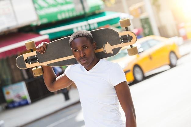 Garoto negro andando na cidade segurando longboard