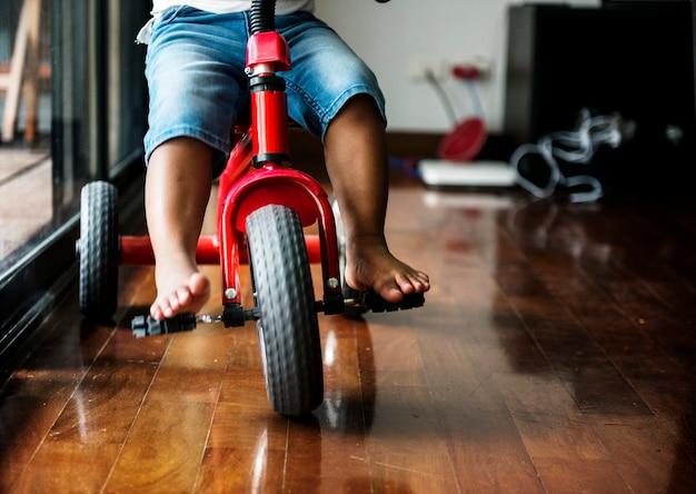 Garoto negro, andar de bicicleta na casa