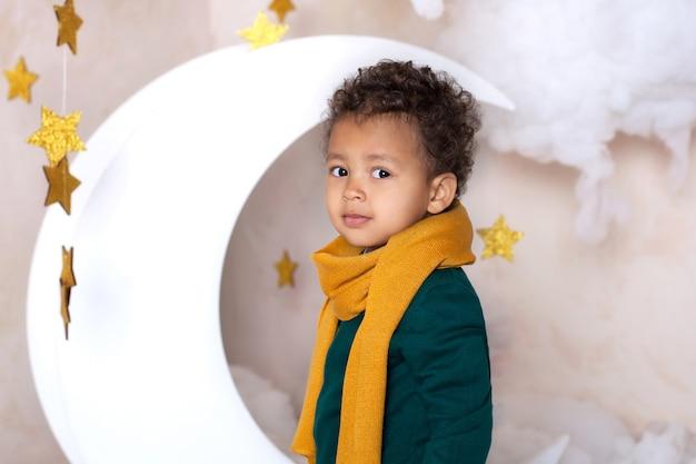 Garoto negro de perto. retrato de um menino preto sorridente alegre em um lenço amarelo. retrato de um pouco de americano africano. cara negro. criança pensativa. infância. criança brinca no jardim de infância. carinha de menino