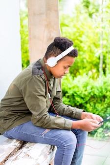 Garoto negro, ouvindo música com fones de ouvido