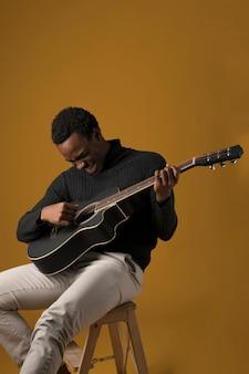 Garoto negro tocando guitarra