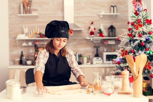 Garoto no dia de natal fazendo uma sobremesa saborosa com massa
