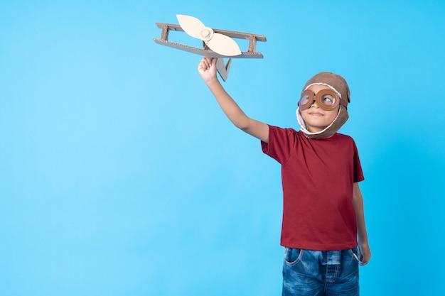 Garoto no sonho de camisa vermelha como piloto segurando papel de avião