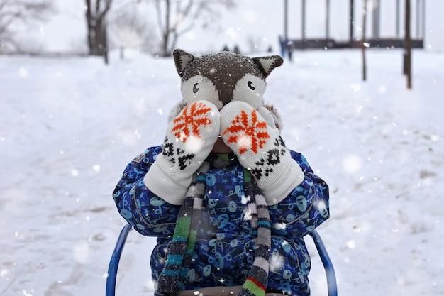 Garoto no trenó no parque de inverno