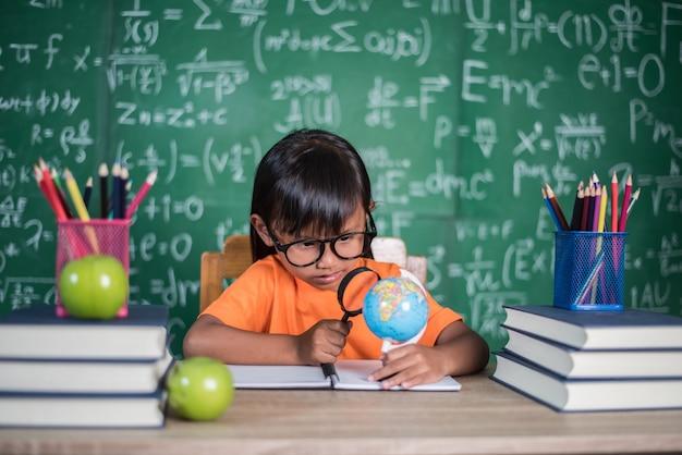Garoto observando ou estudando modelo de globo educacional na sala de aula.