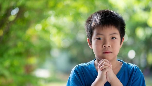 Garoto orando pela manhã, mãos cruzadas em oração