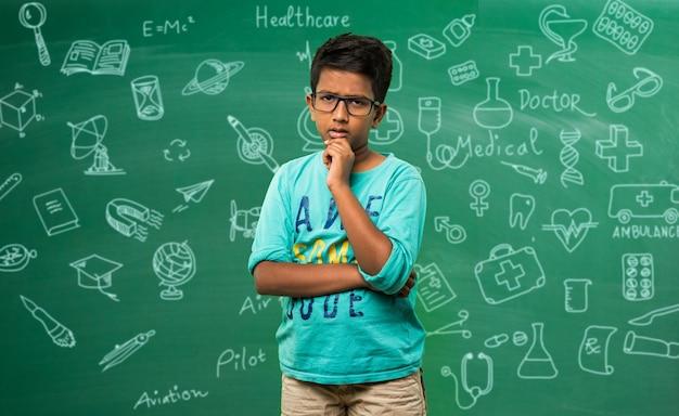 Garoto ou garoto indiano asiático expressivo em frente a uma lousa verde com rabiscos