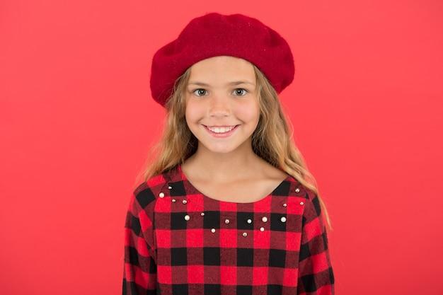 Garoto pequena linda garota sorridente rosto posando em fundo de chapéu vermelho. acessório de boina elegante para mulheres. como usar uma boina francesa. inspiração do estilo boina. como usar a boina como uma garota fashion.
