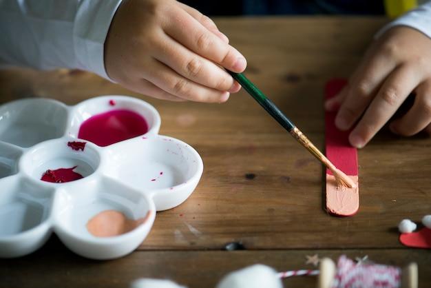Garoto pintando em uma vara de sorvete