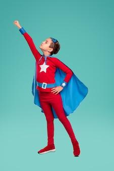 Garoto poderoso de corpo inteiro em fantasia de super-herói cerrando os punhos e se preparando para voar contra o turquesa