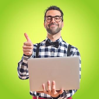 Garoto posh com laptop sobre fundo branco em fundo colorido